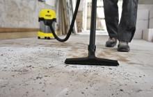 Мужчина чистит пыль промышленным пылесосом