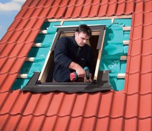 Мужчина устанавливает мансардное окно
