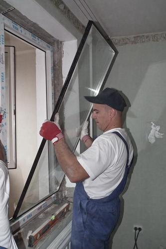 Мужчина устанавливает энергосберегающий стеклопакет