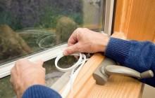 Мужчина утепляет окно