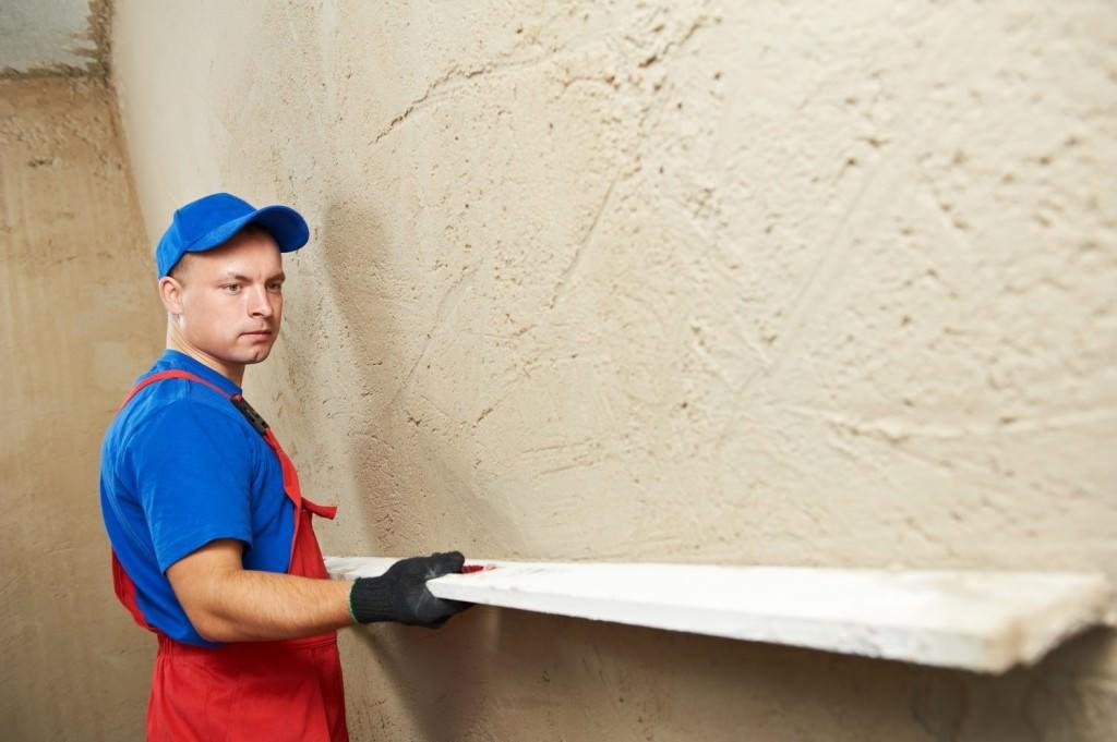 Мужчина выравнивает стену