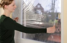 Женщина утепляет окно плёнкой