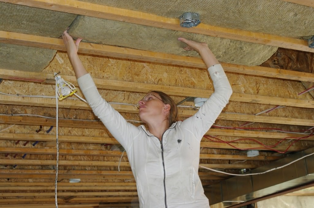 Женщина утепляет потолок в бане