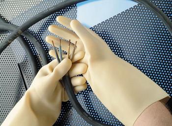 Мужчина держит электрические провода в перчатках