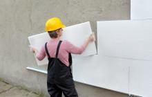 Женщина клеит пенопласт на стену