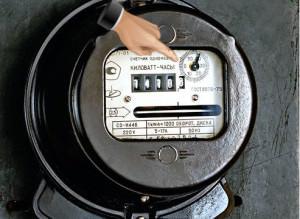 Рука на счетчике электроэнергии