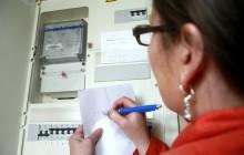 Женщина снимает показания счетчиков электроэнергии