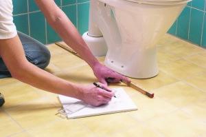 Мужчина чертит место установки тафты для унитаза
