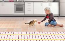 Девочка играет с котом на теплом электрическом полу