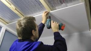 Мужчина устанавливает пластиковые панели на потолок