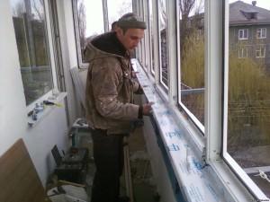 Специалисты устанавливают подоконник на балконе