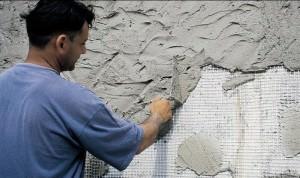 Мужчина наносит фасадную штукатурку