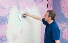 Мужчина шпаклюет стену под обои
