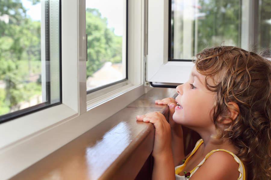 Девочка смотрит в пластиковые окна