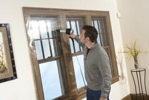Мужчина утепляет окно плёнкой