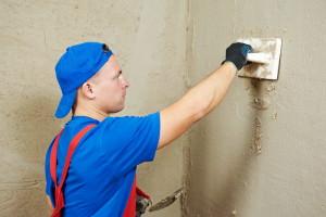 Мужчина штукатурит стену