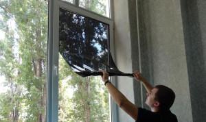 Мужчина тонирует окно плёнкой