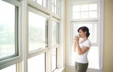 Женщина стоит у окна