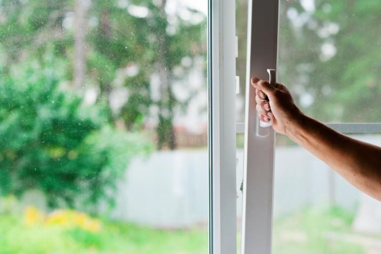 Мужчина открывает пластиковое окно