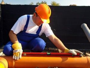 Мужчина измеряет уклон канализационной трубы