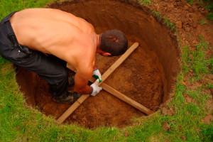 Мужчина помечает место для установки колодца