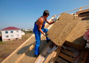 Мужчина утепляет крышу минватой